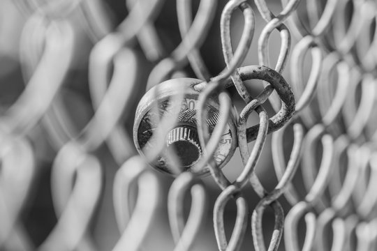 Rusted and broken school combination lock hanging on chain link fence