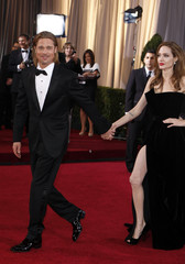 Actor Brad Pitt leads his partner actress Angelina Jolie up the red carpet at the 84th Academy Awards in Hollywood