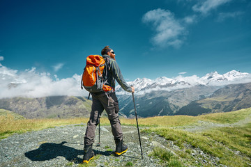 hiker with backpack stands on the trail in the Apls mountains. Trek near Matterhorn mount. Mountain ridge and blue sky on the background Wall mural