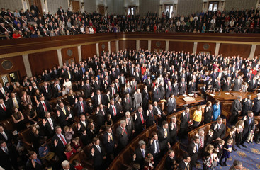 Republican members of the 112th U.S. House of Representatives raise their hands to be sworn into office on the opening day of their session on Capitol Hill in Washington