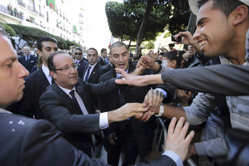 French President Hollande shakes hands with people in the crowd during a walk in Algiers