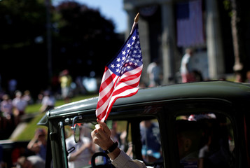Man waves an American flag as he drives an antique car through Barnstable Village, on Cape Cod during July 4th parade