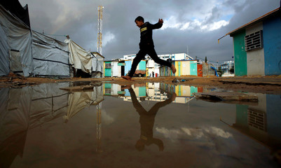 A Palestinian boy who lives in a container as a temporary replacement for his house that was destroyed in the 2014 war, jumps over a flooded path on a rainy day in Beit Hanoun in the northern Gaza Strip