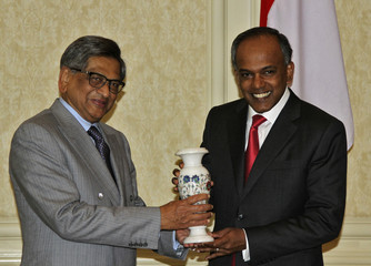 India's FM Krishna presents a flower vase to his Singaporean counterpart Shanmugam during a photo opportunity before their meeting in New Delhi