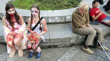 A woman looks at enthusiasts dressed as zombies as they wait for the start of the annual Zombie Walk festival in Prague