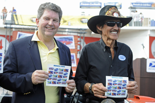 U.S. Postmaster General Donahoe stands with racing legend Petty as they hold the new Muscle Cars Forever stamps after the stamp dedication ceremony at the Daytona International Speedway