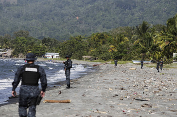 Border police walk along the beach in Masca