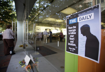 Tribute to Steve Jobs is posted on the window of the Apple store