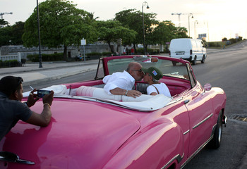 Tourists pose for a photo while sitting in a vintage car in Havana