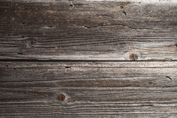Two horizontal weathered timber planks on old wooden building with joint in the middle