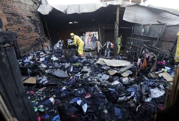"Municipal workers remove burnt debris from the capital's biggest marketplace ""Mercado Cuatro"" in Asuncion"