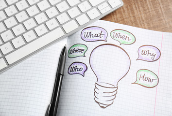 Marketing idea concept. Drawing light bulb in notebook