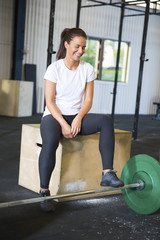 Smiling Athlete Sitting On Box By Barbell In Health Club