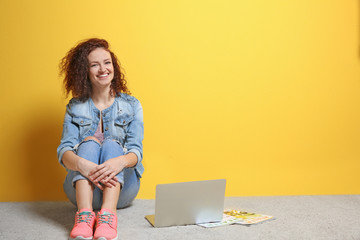 Beautiful young woman with laptop on color wall background