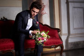 young groom waiting his bride on sofa