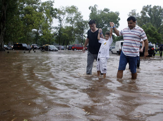 People walk in a flooded street as they leave the ATP Buenos Aires Open after tennis matches were suspended due to rain