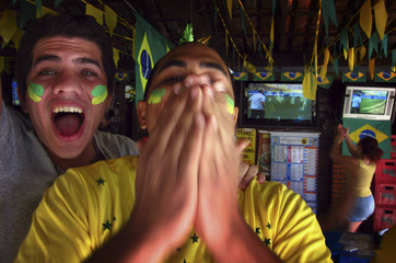 Brazilian supporters celebrate in a small outdoor bar in Brasilia after watching on television their team defeat Chile in their World Cup round of 16 soccer match