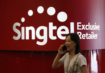 A woman talking on the phone passes by a Singtel reseller shop in Singapore