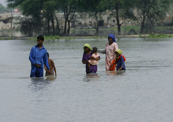 A family walks through flood waters as they return to their village in Karampur