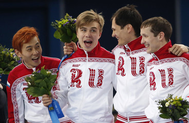 The winning Russian team celebrates on the podium during the flower ceremony for the men's 5,000 metres short track speed skating final relay race at the Iceberg Skating Palace in the Sochi 2014 Winter Olympic Games