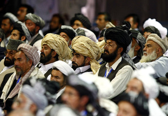 Delegates listen to the opening address of the peace jirga by Afghan President Hamid Karzai in Kabul