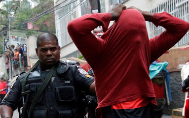 A police officer arrests a suspected drug dealer after a shootout during a police operation at Pavao-Pavaozinho slum in Rio de Janeiro