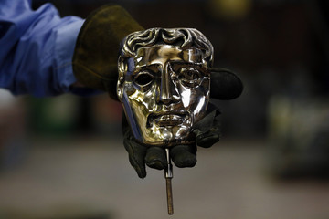 A foundry holds a finished bronze British Academy of Film and Television Awards mask at a foundry in west London