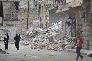 Civilians walk past damaged buildings in rebel-controlled area of Maaret al-Numan town in Idlib province, Syria