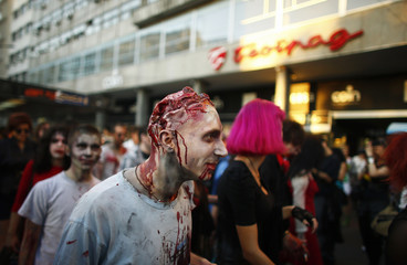 An actor dressed as a zombie parades on a street during a zombie walk in Belgrade