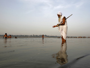 A Sadhu or a Hindu holy man offers milk to the waters of holy river Ganga as part of his morning prayers in Allahabad