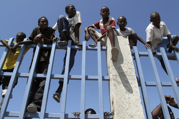 Haitian children sit on a fence at a camp in downtown Port-au-Prince