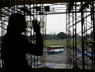A worker takes a break in a building across from the Quirino grandstand where a bullet-riddled tourist bus is still parked three days after a hostage drama in Manila