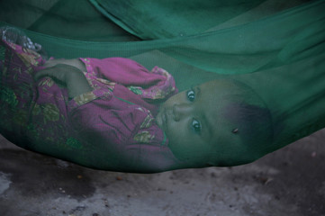 Nazia lies in a hammock while taking refuge with her family at a camp for flood victims in the Badin district of Pakistan