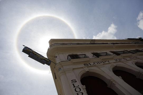 "An atmospheric phenomenon known as a ""sun dog"" is seen beside Sloppy Joe's bar in the sky over Havana"
