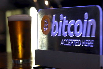A beer poured for a customer sits on a bar next to a Bitcoin sign in central Sydney, Australia