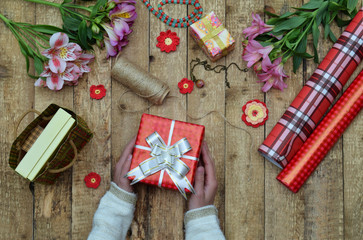 Festive background. Top view composition of woman hands wrap present for Birthday, Mother's day, Valentine's Day, March 8. Packed gifts and flowers, wrapping paper and tools on shabby wooden table.