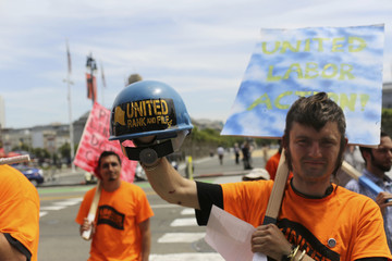 Union worker Elliot Hughes displays his helmet as he joins other workers on the steps of City Hall during an International Worker's Day rally in San Francisco, California