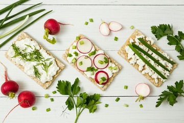 Vegetarian toast with cottage cheese, herbs and radish on a white background.