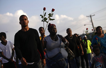Demonstrators holding roses protest against the shooting death of Michael Brown in Ferguson, Missouri