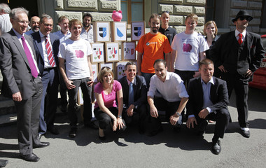 Committee members pose next to boxes with signatures of referendum against book price control  in Bern