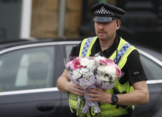 A police officer carries bunches of flowers at the scene of the murder of Labour MP Jo Cox in Birstall near Leeds