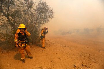 Firefighters shield themselves from high winds as the Blue Cut fire burns in Phelan
