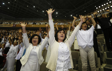 Believers give three cheers as they attend the first death anniversary of evangelist Reverend Moon by the lunar calendar, in Gapyeong