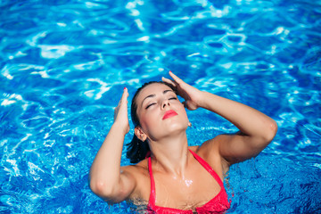 A Sexy girl is swimming in the swimming pool  near the beach, sunny weather. Summer