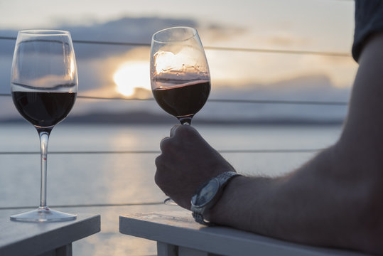 Romantic wine close up couple sitting at sunset on deck drinking