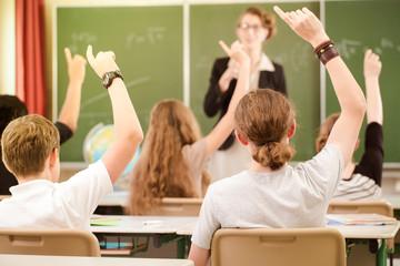 Lehrerin oder Dozent steht im Unterricht vor einer Tafel und unterrichtet Schüler, die sich melden und lernen in einer Klasse oder Schule