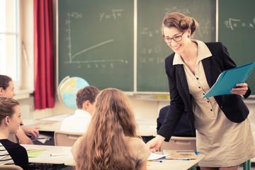 Lehrer teilt Arbeit an Klasse in Schule aus