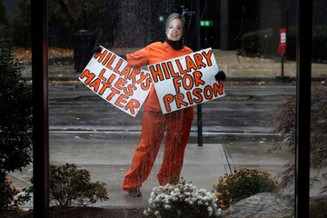 A person wearing an orange jumpsuit and dressed as Hillary Clinton stands outside the venue of U.S. Republican presidential nominee Donald Trump's campaign event in Manchester