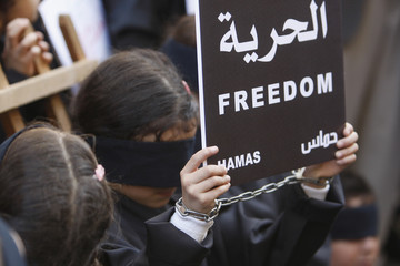A Palestinian girl with hands chained and blindfolded eyes carries a placard during a protest calling for the release of Arab and Palestinian prisoners from Israeli jails, near the ICRC offices in Beirut