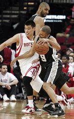 San Antonio Spurs guard Tony Parker drives past Houston Rockets guard Jeremy Lin as Spurs forward Tim Duncan sets the pick during their NBA basketball game in Houston